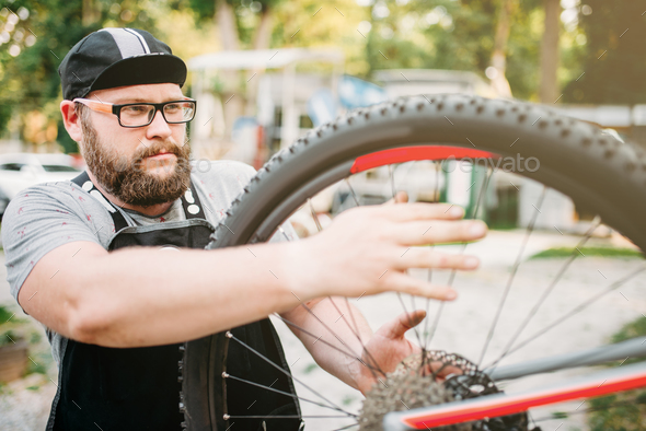 Bicycle repairman works with bike wheel - Stock Photo - Images