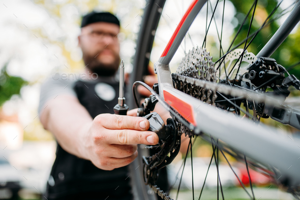 Bicycle mechanic repair bike with broken shifter - Stock Photo - Images