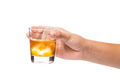 Hand holding a glass of whiskey on the rock