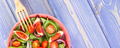 Fresh fruit and vegetable salad with fork, concept of healthy food and nutrition