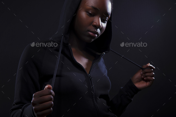 Cool and pensive woman with dark skin and attitude wearing hoodie - Stock Photo - Images
