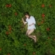 CRANE MOTION: Young Woman Lying in Green Grass Among Poppies - VideoHive Item for Sale