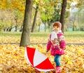 A little girl walking in the park with an umbrella