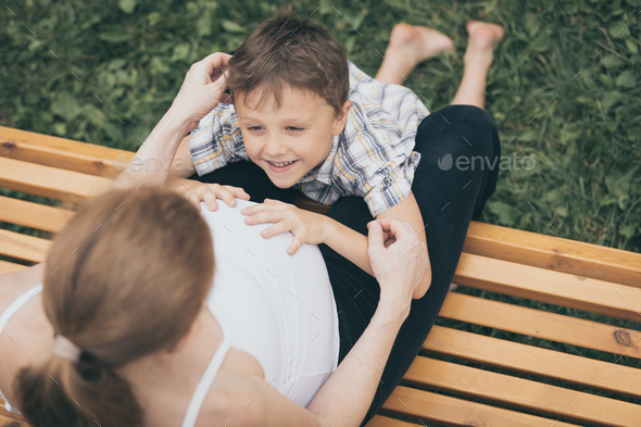 Happy little boy hugging mother in the park at the day time. - Stock Photo - Images