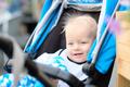 Baby boy sitting in modern stroller