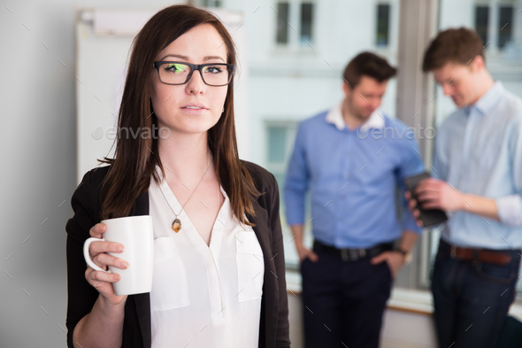 Businesswoman Holding Coffee Mug While Colleagues Discussing In - Stock Photo - Images