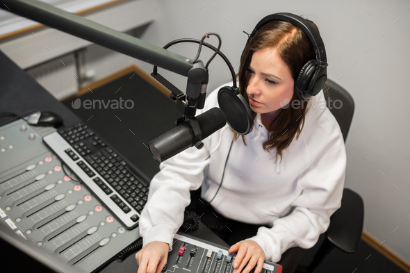 Radio Jockey Using Music Mixer While Communicating On Microphone - Stock Photo - Images
