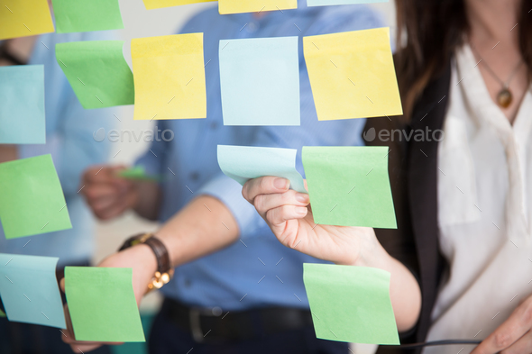 Midsection Of Business People Sticking Adhesive Notes On Glass - Stock Photo - Images