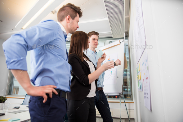 Professionals Looking At Plans Stuck On Wall In Office - Stock Photo - Images