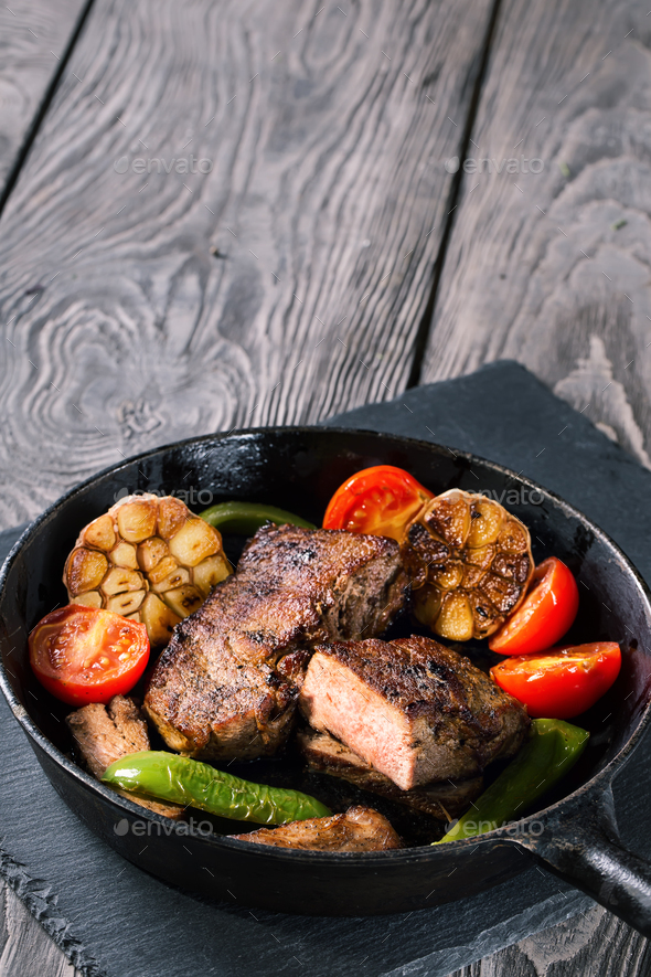 Slightly fried beef steak with vegetables on cast-iron frying pa - Stock Photo - Images