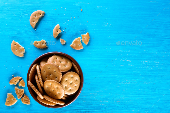 A bowl with crispy crackers on a blue background - Stock Photo - Images