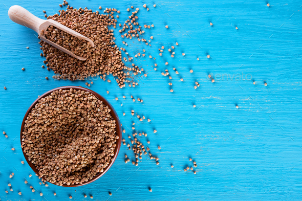 Clay bowl with buckwheat croup on a blue background - Stock Photo - Images