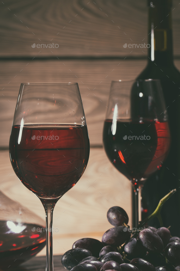 Two glasses and a bottle of red wine and grapes on the table - Stock Photo - Images