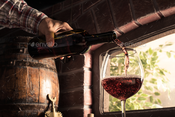 Sommelier pouring wine into a glass - Stock Photo - Images