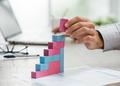 Businessman building a growing financial graph - PhotoDune Item for Sale