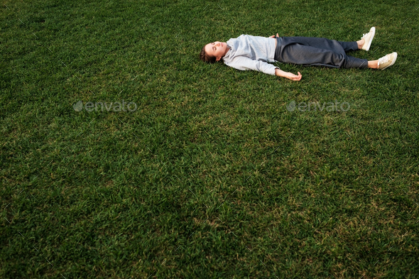 Beautiful young european woman lays down on grass and rests