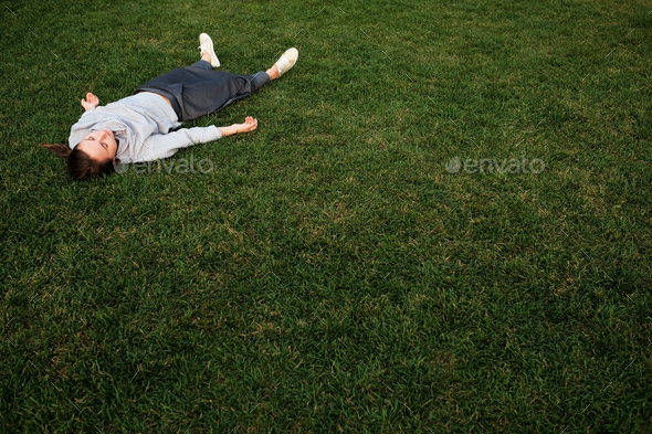 Beautiful young european woman lays down on grass and rests - Stock Photo - Images