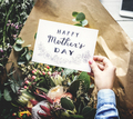 Hands Holding Happy Mother Day Greeting Card with Flowers Bouque