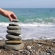 Woman's Hand Puts Pebble in Pyramid on the Sea - VideoHive Item for Sale