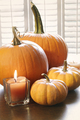 Pumpkins with candle on table near window - PhotoDune Item for Sale