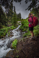 Hiking Colorado Girl Backpacker looks at cascading creek near la