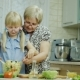 Girl of 6 Years Together with the Grandmother Do a Salad in Kitchen - VideoHive Item for Sale