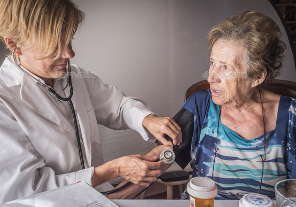Doctor measures the arterial tension to oldster at home, Andalusia, Spain - Stock Photo - Images