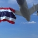 Commercial Airplane Landing Behind Waving Thai Flag