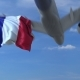 Commercial Airplane Landing Behind Waving French Flag