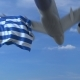 Commercial Airplane Landing Behind Waving Greek Flag
