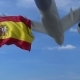 Commercial Airplane Landing Behind Waving Spanish Flag
