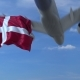 Commercial Airplane Landing Behind Waving Danish Flag