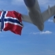Commercial Airplane Landing Behind Waving Norwegian Flag