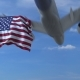 Commercial Airplane Landing Behind Waving American Flag