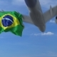 Commercial Airplane Landing Behind Waving Brazilian Flag