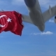 Commercial Airplane Landing Behind Waving Turkish Flag