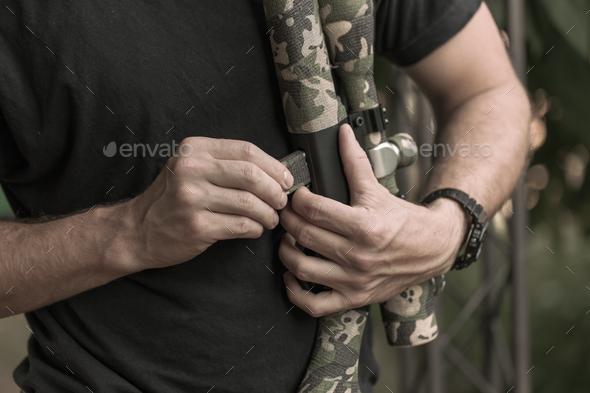 Hunter loading his gun - Stock Photo - Images