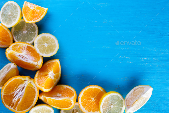 Blue background filled with fresh sliced fruit - Stock Photo - Images