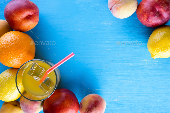 Fresh juicy fruit and cold juice on blue wooden table - Stock Photo - Images