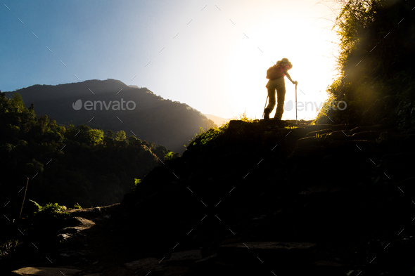 Female in silhouette hiking at highland towards sunrise. Lens flare intended - Stock Photo - Images