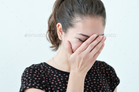 Playful shy woman hiding face with her hands - Stock Photo - Images