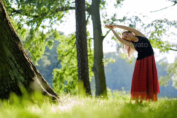 Attractive young female in red skirt is practicing yoga and doing asana in the morning. - Stock Photo - Images