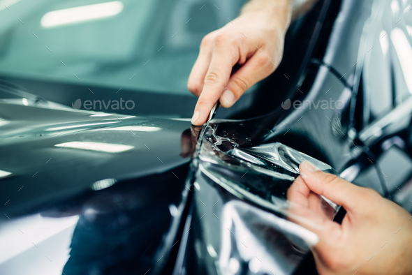 Worker hands installs car paint protection film - Stock Photo - Images