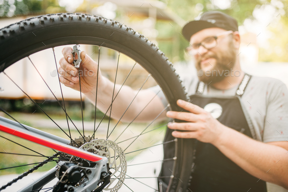 Bicycle mechanic in apron adjusts bike spokes - Stock Photo - Images