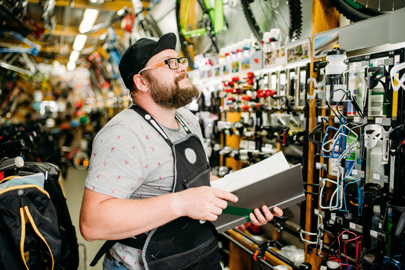 Bicycle mechanic with notebook in bike shop - Stock Photo - Images
