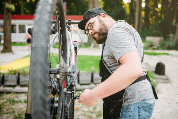 Repairman works with bike wheel, cycle workshop - Stock Photo - Images