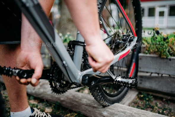 Bicycle mechanic hands adjusts cycling pedals - Stock Photo - Images