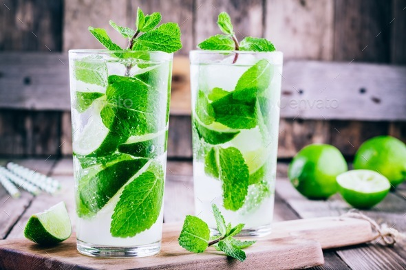 fresh mojito cocktails with lime, mint and ice in glass - Stock Photo - Images