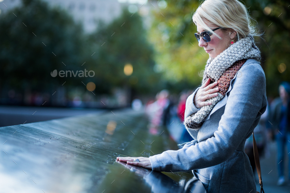 Sad woman looking at the Names of World Trade Center Memorial - Stock Photo - Images
