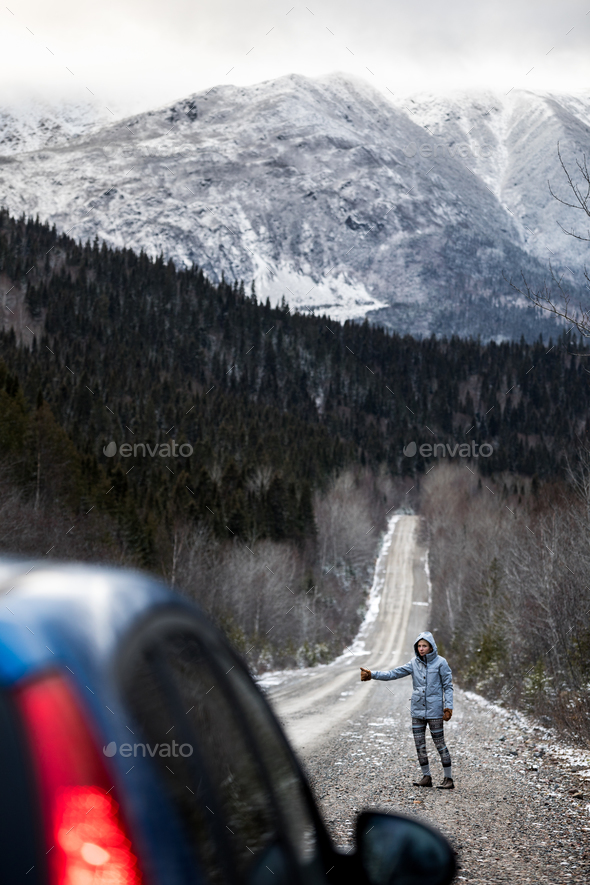 Woman Hitchhiking on a Winter Road with Beautiful Snowy Mountain - Stock Photo - Images